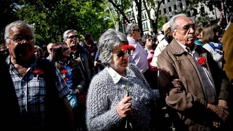 Ativistas seguram cravos vermelhos nesta sexta-feira (25), durante a marcha que celebra os 40 anos da Revolução dos Cravos, em Portugal