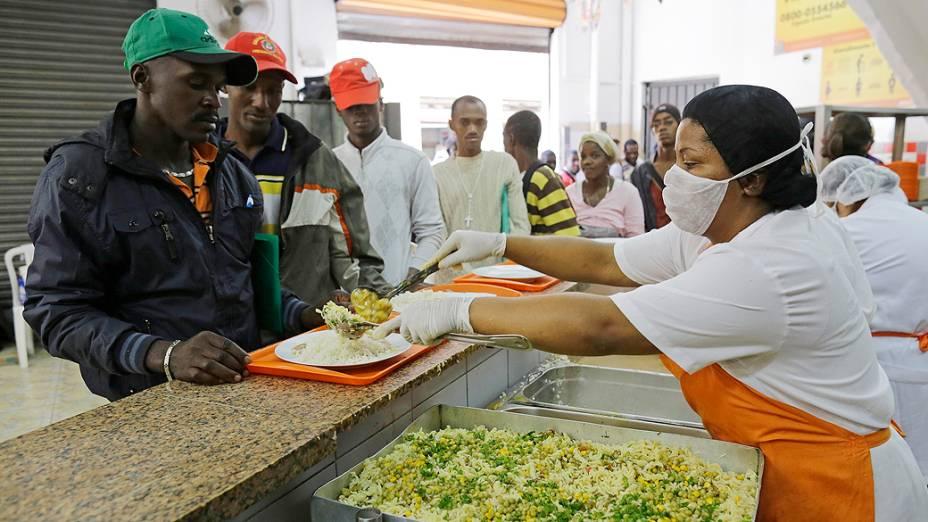 Refugiados haitianos fazem fila para almoçar no restaurante Bom Prato na manhã desta terça-feira (29), na Igreja Nossa Senhora da Paz, no Glicério, região central