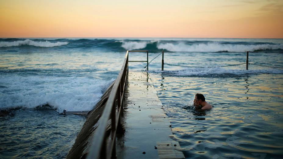 Homem lava o rosto em uma piscina à beira do Oceano Pacífico durante o entardecer em Cronulla Beach, Sydney