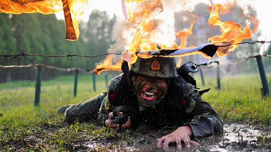 Um policial paramilitar rasteja sob obstáculos durante treinamento na base militar em Chaohu, província de Anhui, na China