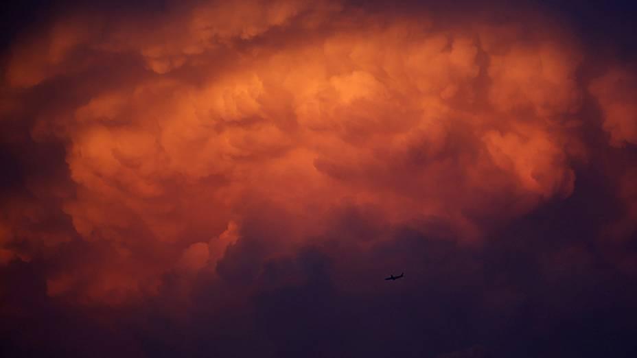 Avião fotografado sob uma nuvem de tempestade ao amanhecer em Bangcoc, na Tailândia