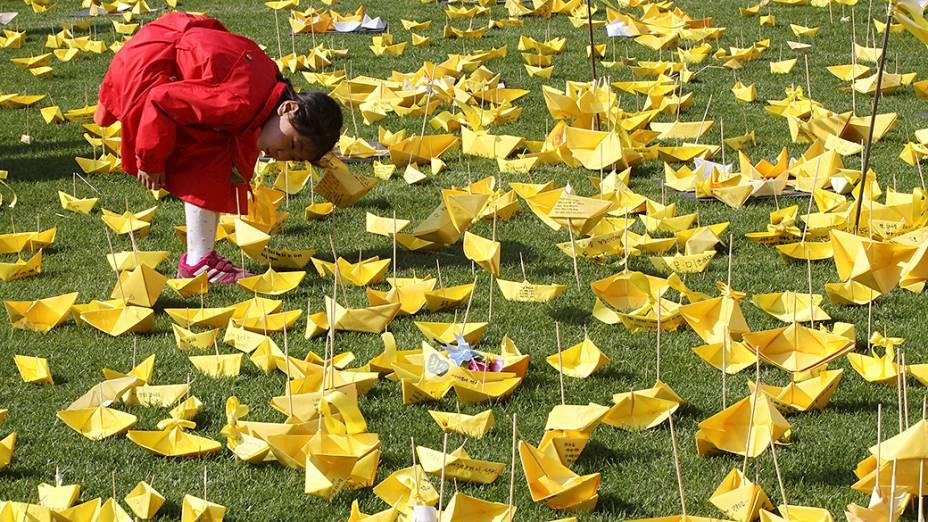 Menina lê mensagens escritas em barquinhos de papel homenageando as vítimas do naufrágio da balsa Sewol em um memorial na cidade de Seul, na Coreia do Sul