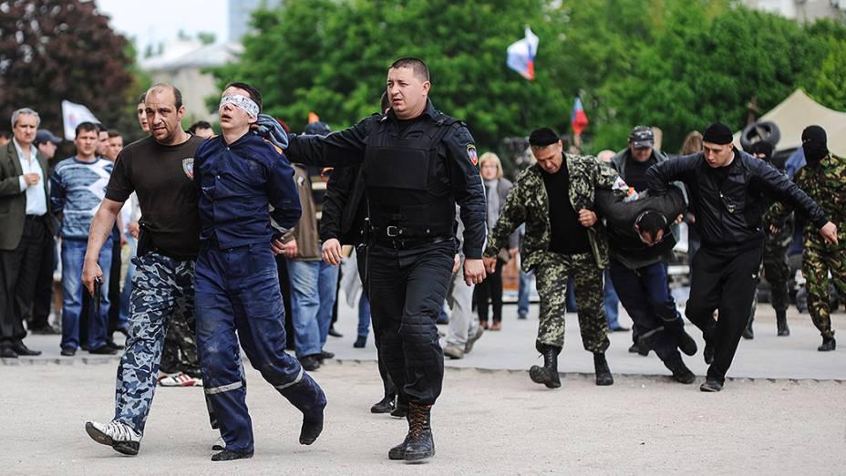 Ativistas pró-Rússia conduzem um funcionário do serviço de incêndio com os olhos vendados, para o prédio da administração regional na cidade de Donetsk, na Ucrânia