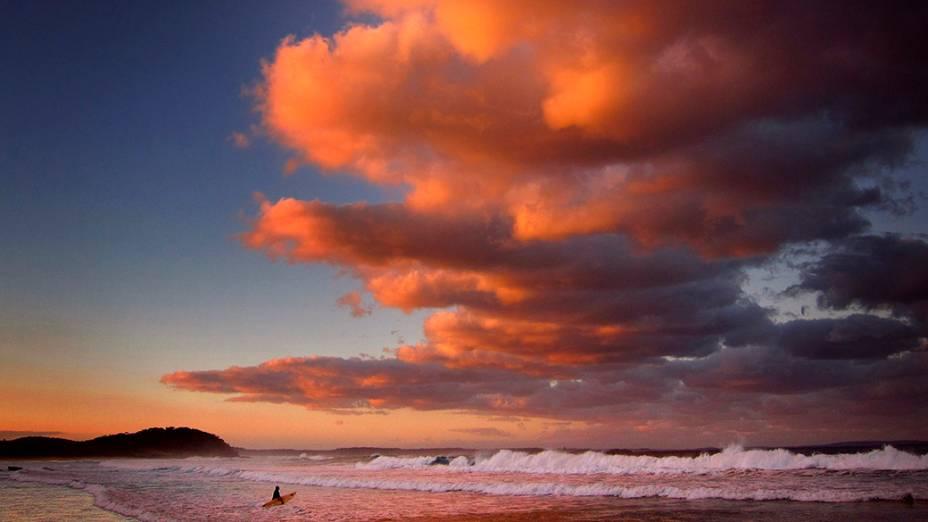 Surfista segura sua prancha durante o por-do-sol em Mollymook Beach, na Austrália