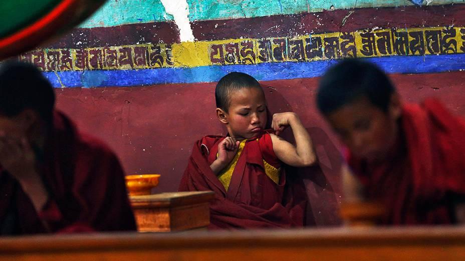 Jovem monge budista flexiona os músculos durante as orações da manhã no Mosteiro Thikse em Ladakh, na Índia