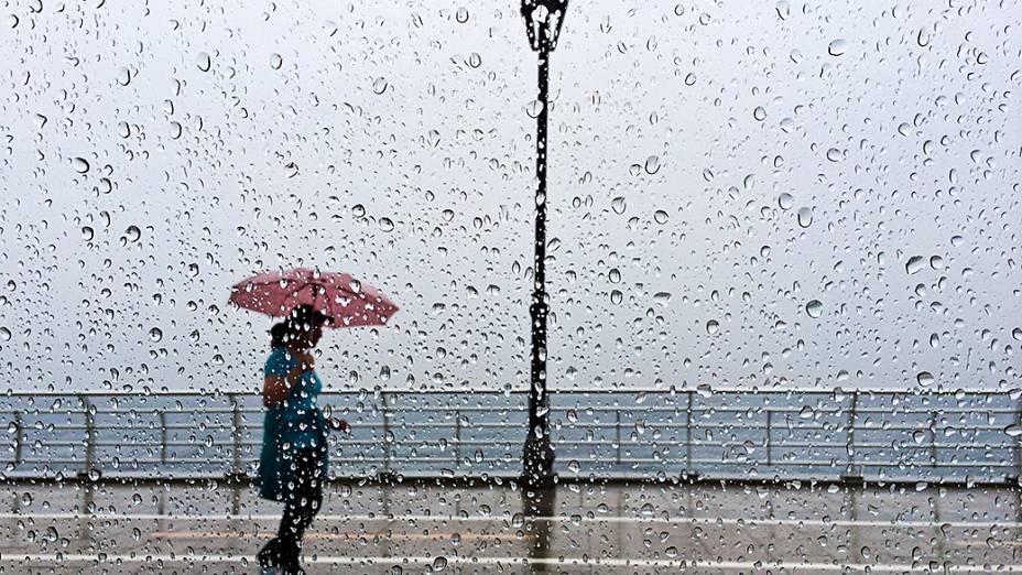 Mulher se abriga sob seu guarda-chuva em Beirute, Líbano