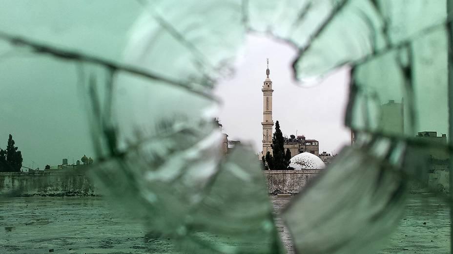 Mesquita fotografada através de um vidro quebrado na antiga cidade de Homs, na Síria. Rebeldes se retiraram do centro da cidade após três anos de combates