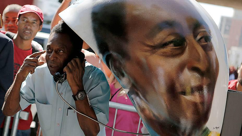 Pelé posa ao lado de um orelhão com seu rosto pintado pelo artista brasileiro Sipros, em São Paulo