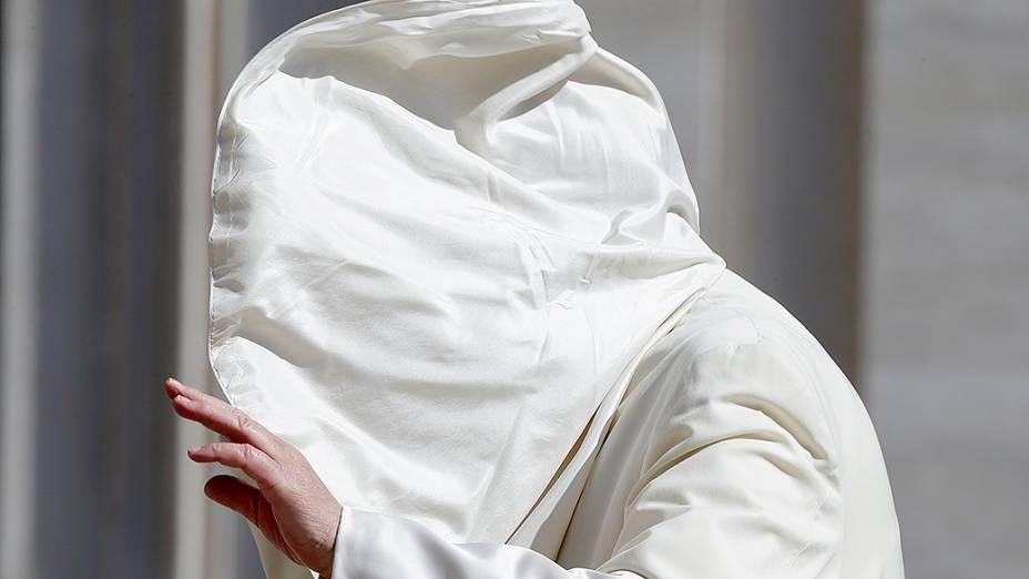 O papa Francisco ficou com o rosto coberto após encarar uma rajada de vento na chegada para a audiência semanal na Praça de São Pedro, no Vaticano