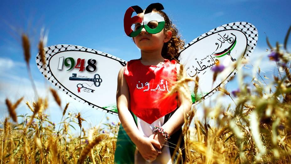 Criança palestina veste roupas em referência ao Dia de Nakba, que marca a expulsão de palestinos de suas terras por tropas israelenses em 48