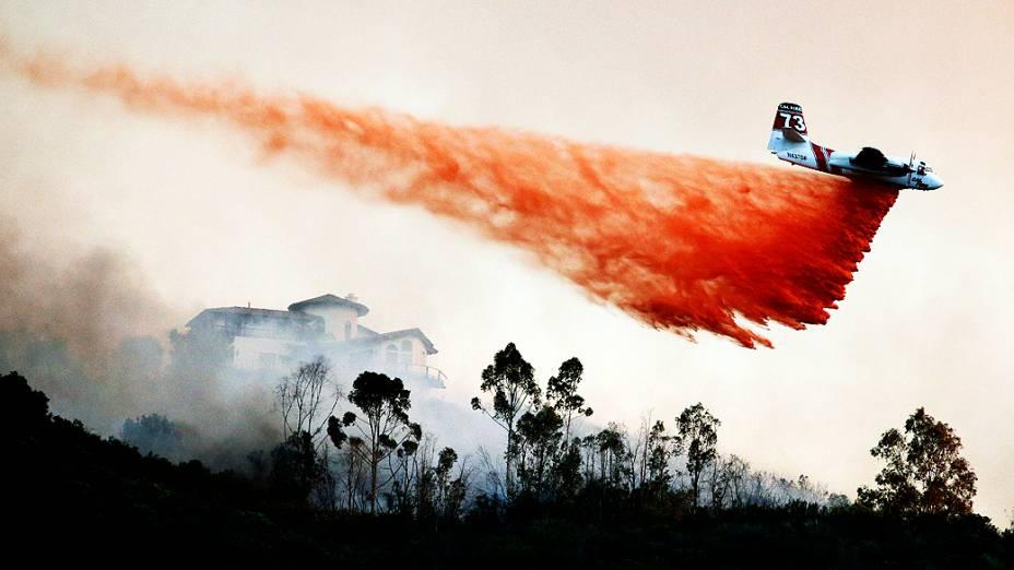 Avião joga água para tentar controlar incêndio florestal de grande proporção no subúrbio de San Marcos, California (EUA), nesta quinta-feira (15)