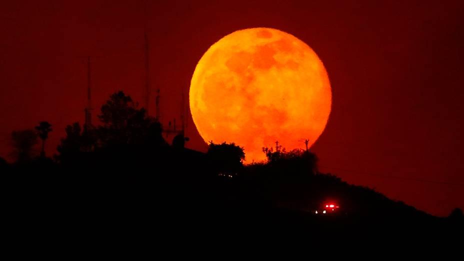 Veículo de emergência trafega durante a lua crescente ao longo de uma encosta queimada perto de San Marcos, na Califórnia