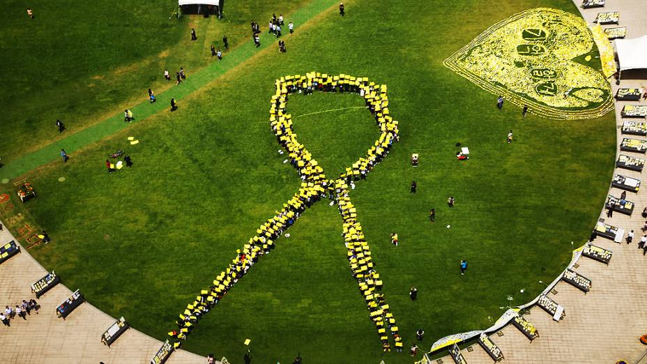 Pessoas formam uma fita amarela gigante, diante de memorial em Seul (Coreia do Sul), em homenagem às vítimas do naufrágio da balsa Sewol