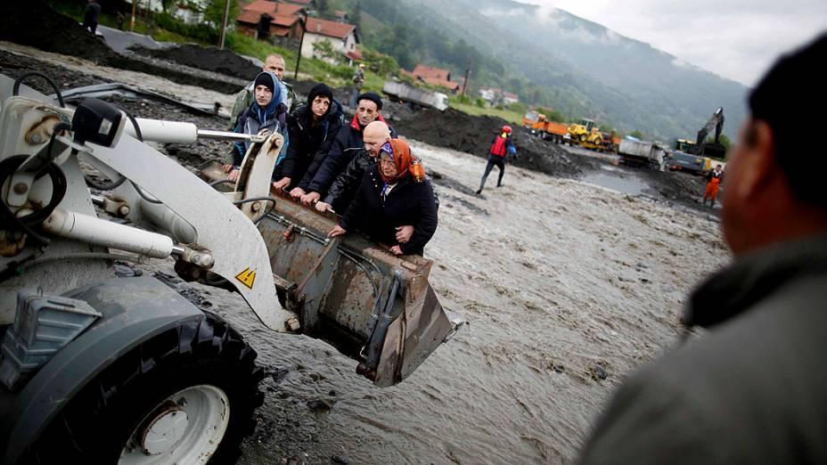 Pessoas são retiradas de suas casas na aldeia de Topcic Polje, perto da cidade bósnia de Zenic, após fortes chuvas na região