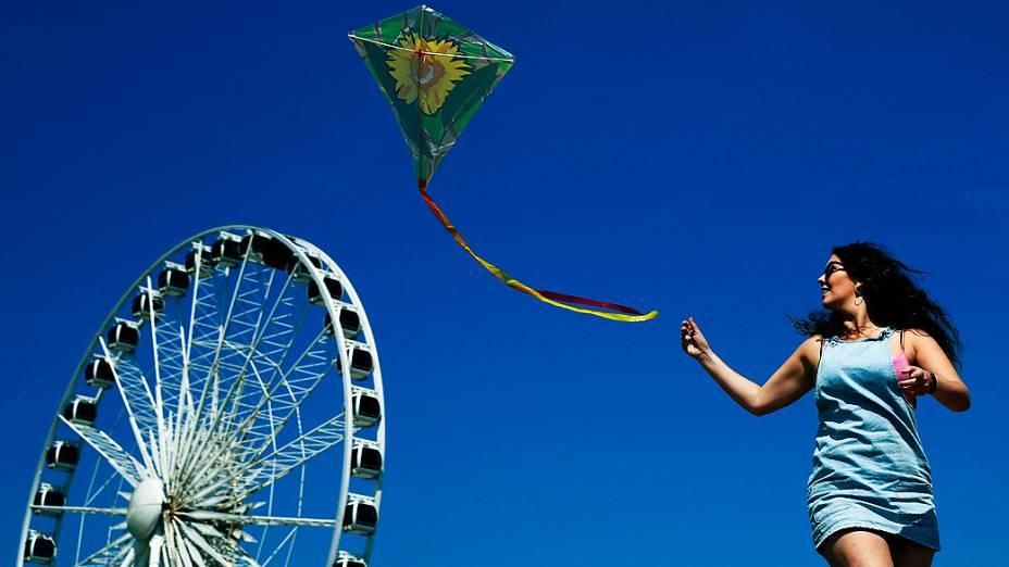Mulher empina pipa em dia ensolarado na praia de Brighton, no sul da Inglaterra, nesta sexta-feira (16)