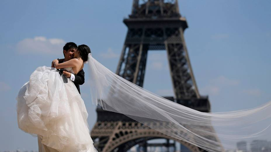 Um casal de noivos posa para o fotógrafo em frente a torre eiffel, em Paris, França