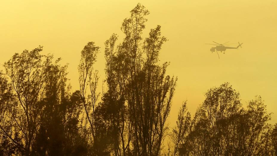 Um helicópeto transporta água durante um incêndioque provocou dezenas de ordens de evacuação e destruiu casas na cidade de Escondido, Califórnia