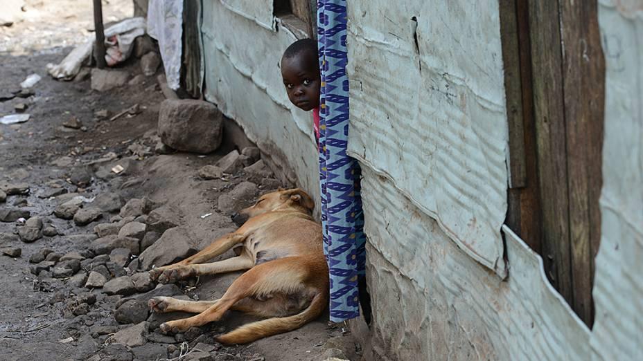Menino espia a rua pela porta em Mathare, a segunda maior favela do Quênia