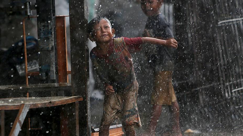 Criança brinca na chuva durante uma tempestade na Indonésia