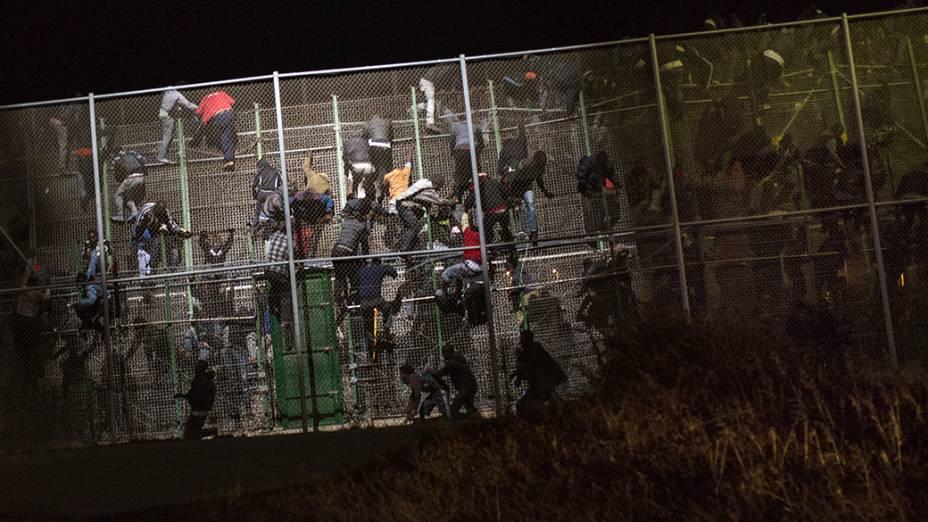 Imigrantes africanos tentam cruzar a fronteira que separa Marrocos da cidade de Melilla, na Espanha