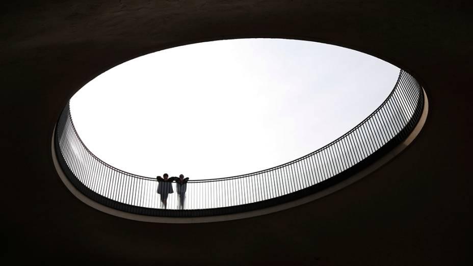 No Japão, homens olham por buraco na frente de um edifício em Tóquio