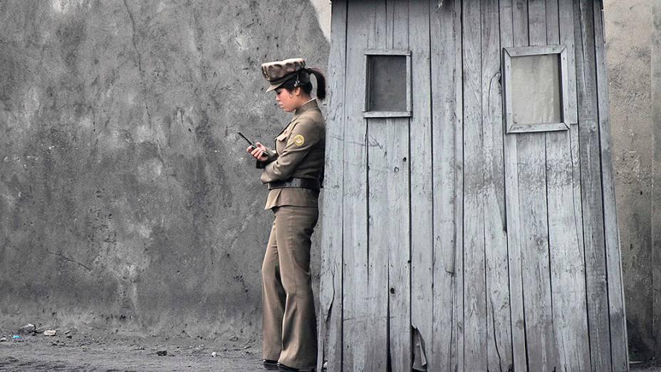 Soldado norte-coreana usa o seu telefone celular ao lado de um posto de vigilância às margens do rio Yalu, próximo à fronteira com a China