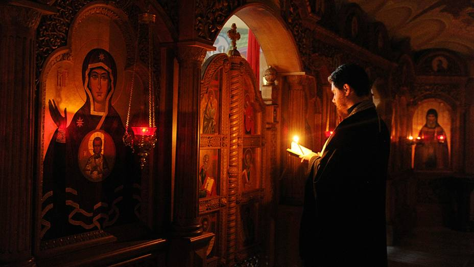 Sacerdote faz orações pelas vítimas da violência entre o exército nacional ucraniano e militantes separatistas pró-Rússia, na catedral Svyato-Preobrazhenski em Donetsk