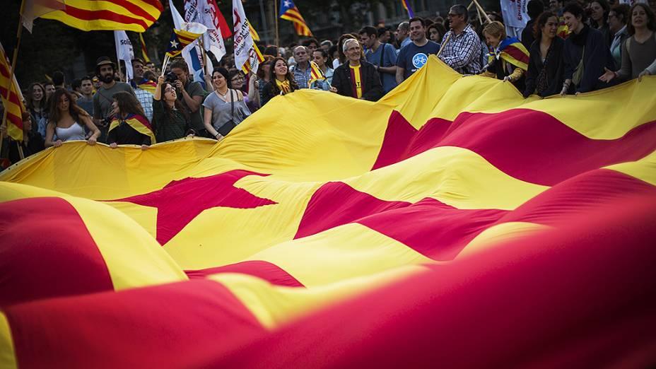 Manifestantes seguram uma enorme bandeira estelada durante protesto pela independência e a implantação da república na Catalunha após o anúncio da abdicação do rei da Espanha Juan Carlos, em Barcelona, na Espanha