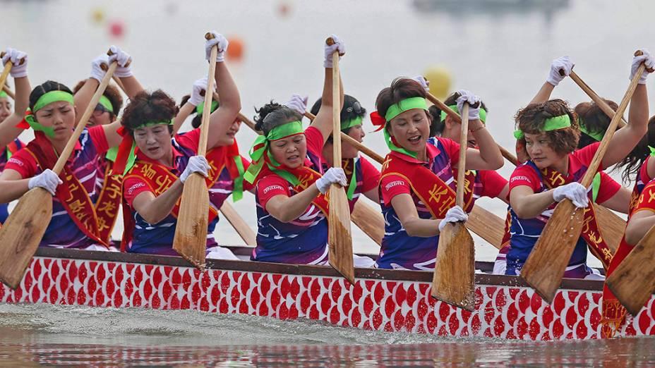 Participantes remam um barco dragão durante competição para celebrar o Festival do Barco na cidade de Yibin, sul da China