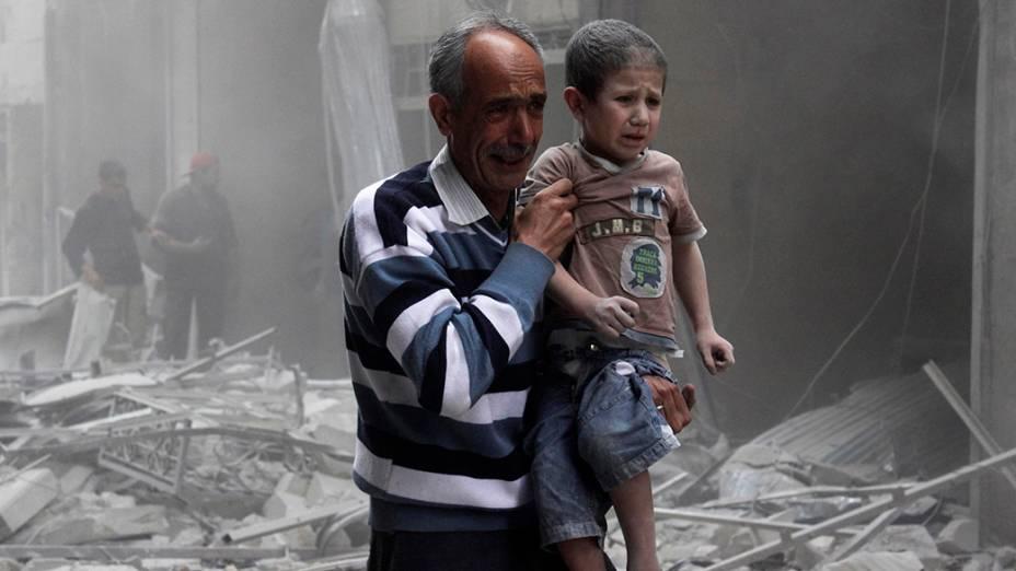 Na cidade de Alepo, homem segura garoto após um ataque aéreo por forças leais ao ditador sírioBashar Assad
