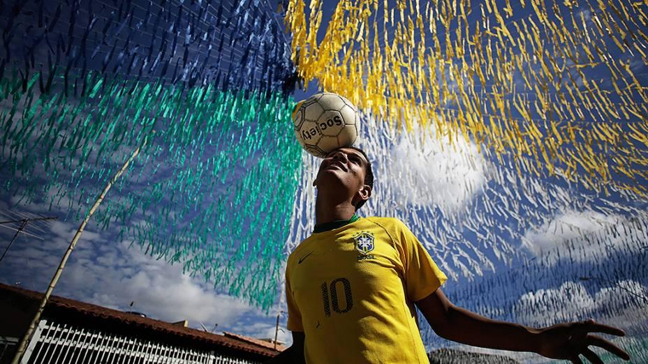 Jovem jogou bola em uma rua decorada para a Copa do Mundo, em Ceilândia, Brasília