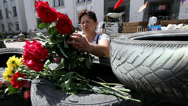 Mulher colocou flores sobre uma barricada em frente ao prédio estatal tomado por separatistas na cidade ucraniana oriental de Lugansk