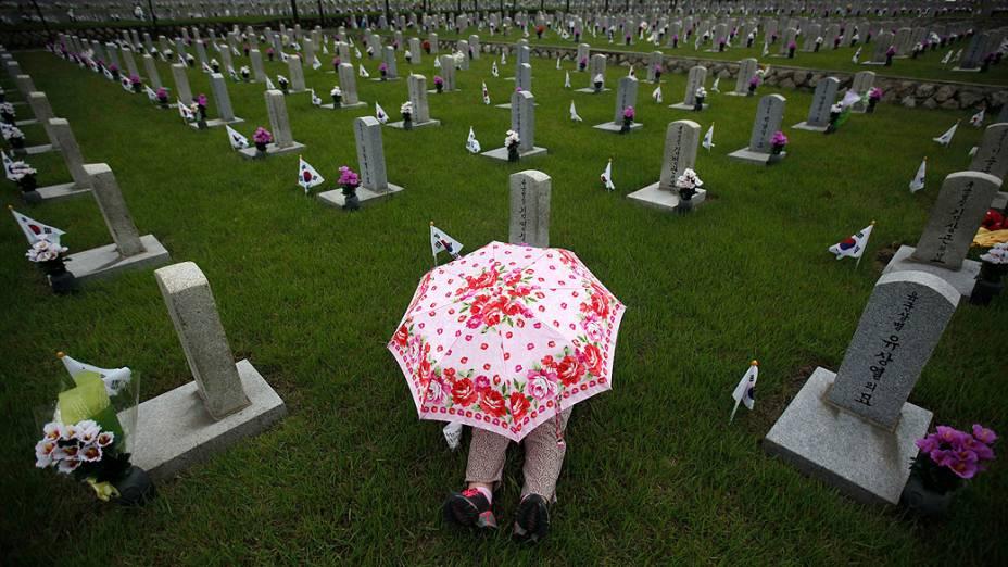 Mulher senta em frente ao túmulo de um familiar no cemitério nacional em Seul, na véspera do Dia da Memória da Coreia do Sul, que homenageia pessoas que morreram pelo país