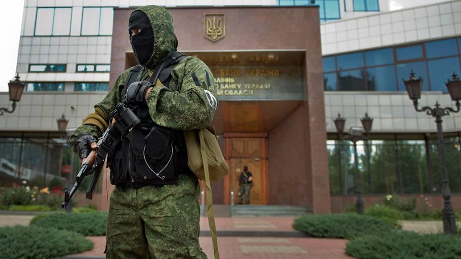 Soldado pró-Rússia fica de guarda do lado de fora do Banco Nacional da Ucrânia após a apreensão do edifício em Donetsk, ao leste do país;A ação é umatentativa de ganhar controle sobre seus ativos