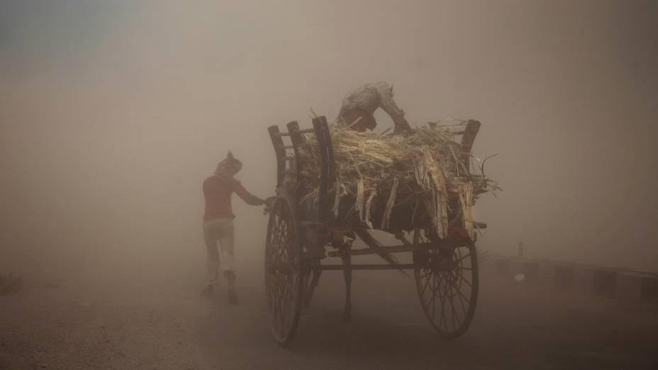 Homens caminham em meio auma tempestade de areia na cidade de Jammu,Índia