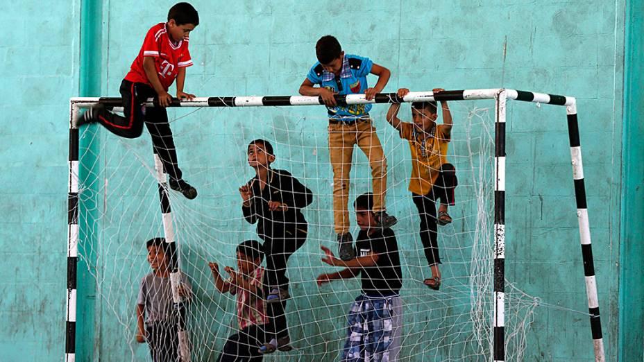 Crianças sírias e palestinas subiram em uma trave antes do início de uma partida de futebol no campo de refugiados Al-Baqaa, na Jordânia