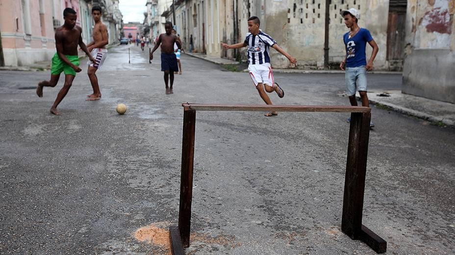 Grupo de adolescentes joga futebol em uma rua de Havana, em Cuba