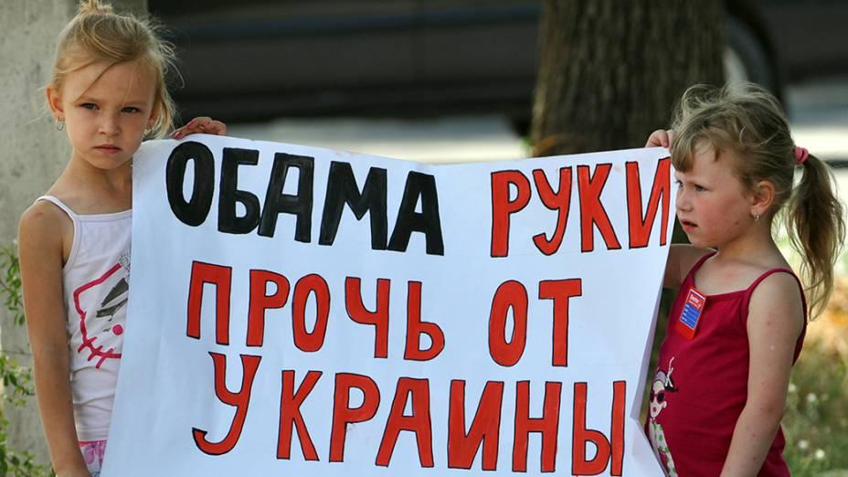 Em frente a embaixada da Ucrânia, crianças seguram um cartaz que diz Obama mãos fora da Ucrânia referindo-se ao presidente dos Estados Unidos durante um protesto contra ações das autoridades ocidentais em Kiev