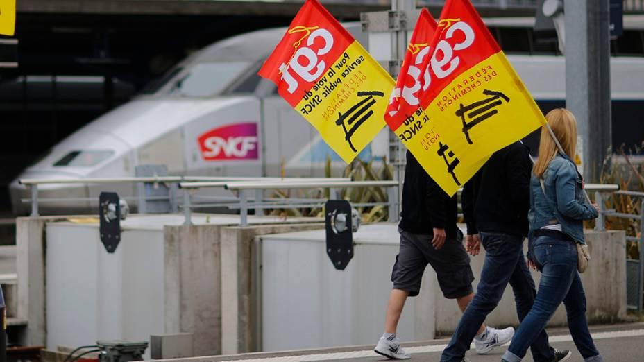 Trabalhadores da ferroviária estatal francesa continuam em greve; Na imagem, manifestantes carregam bandeiras sindicais em protesto contra as reformas previstas pelo governo