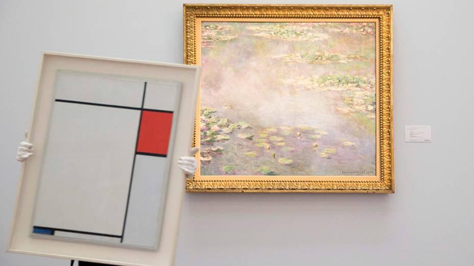 Composição do artistaPiet Mondrian é fotografadaao lado da obra deClaude Monet; A exposição faz parte de um leilão que acontece em Londres, na Inglaterra