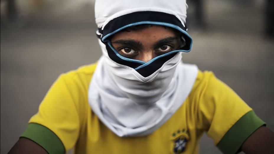 Garotovestindo uma camisa da seleçãobrasileira de futebol é fotografadodurante confrontos entre a polícia emanifestantes anti-governo, na cidade de Isa, no Barein