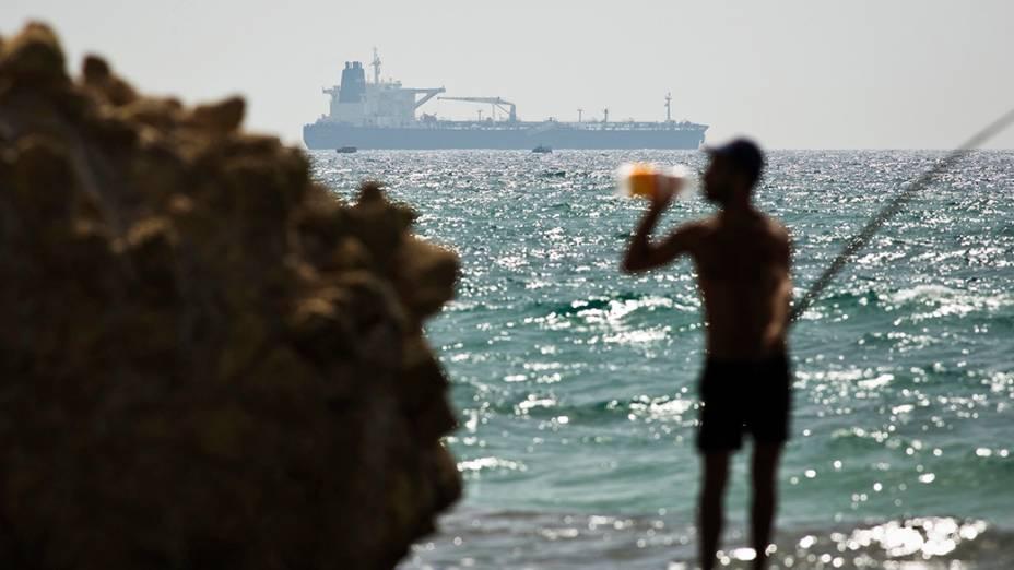 Naviopetroleiro é fotografado afrente de um pescador,na orla do mar Mediterrâneo, emIsrael