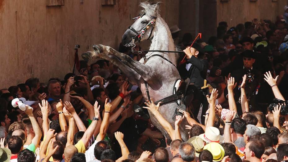 Cavaleiro se ergue em seu cavalo cercado por uma multidão durante os festejos de São João, no centro de Ciutadella, na ilha das Baleares de Menorca, na Espanha