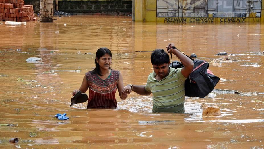Centenas de pessoas estão desabrigadas devido as fortes chuvas no norte daÍndia; Na imagem, moradores percorremuma estrada inundada na tentativa de encontrarum local mais seguro após tempestade,na cidade deGuwahati