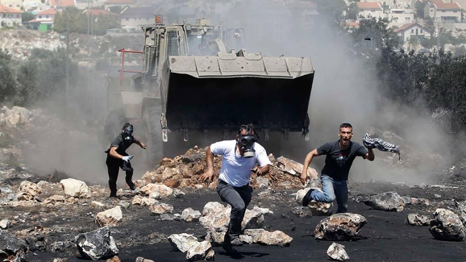Manifestantes correm de uma escavadeira militar israelense durante confrontos com tropas nacionais apósprotesto contra o assentamento judaico, perto da cidade deQadomem, na Cisjordânia