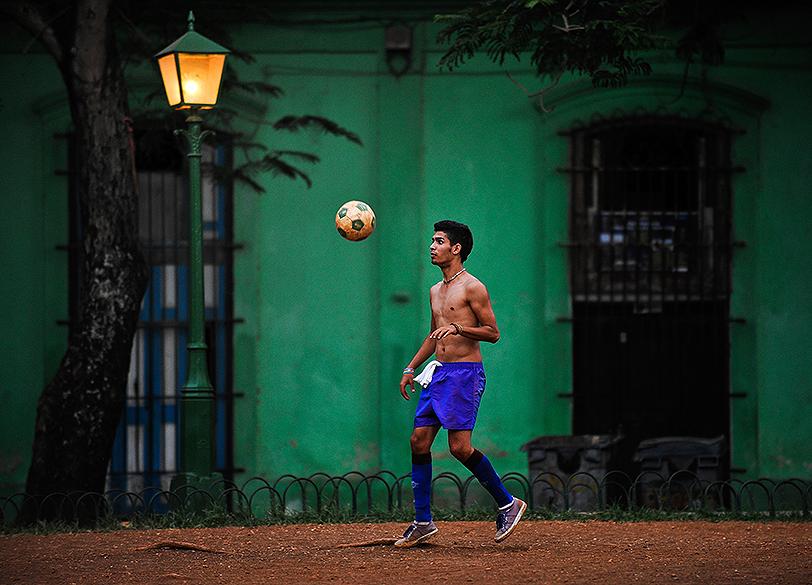 Jovem joga futebol em uma rua de Havana, em Cuba