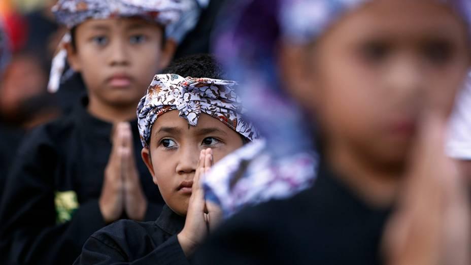 Crianças aguardam a chegada do candidato presidencial da Indonésia, Prabowo Subianto, em um comício de campanha, em Ciparay, ao oeste do país