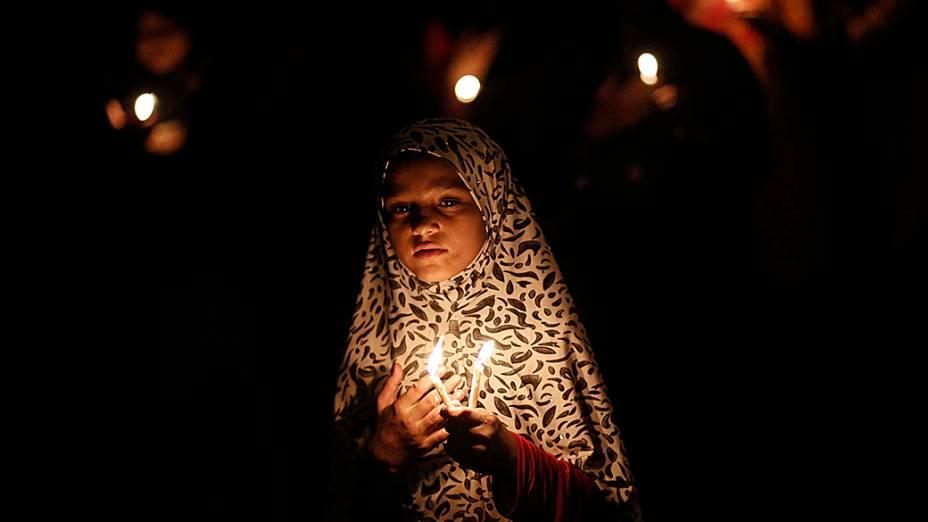 Menina muçulmana xiita participa de um protesto à luz de velas contra o conflito no Iraque, em Nova Delhi, na Índia