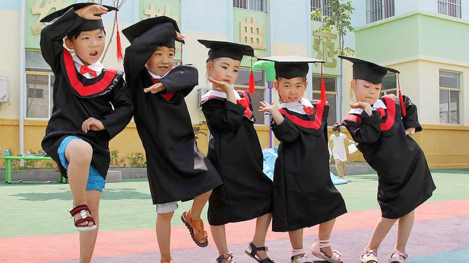 Crianças fazem pose para foto durante cerimônia de formatura do jardim de infância, no condado de Wenxian, província de Henan, na China