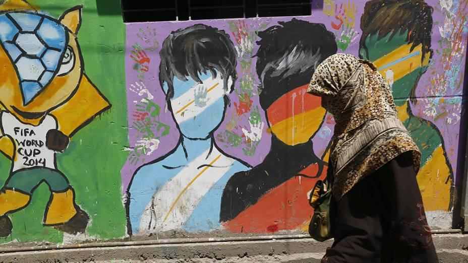 Em Bangladesh, mulher passa por uma parede pintada em homenagem a Copa do Mundo de Futebol, na cidade deDhaka; O mundial termina neste domingo (13)